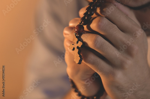 Fototapeta  Religious young man with rosary beads, closeup