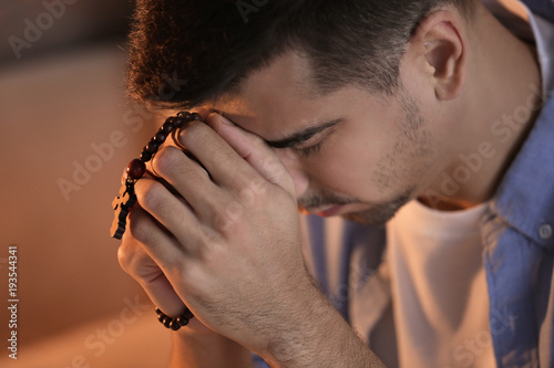 Cuadros en Lienzo Religious young man with rosary beads praying at home, closeup