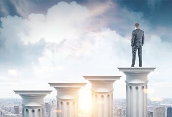 Businessman on a column in a city