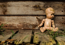 Old Abandoned Plastic Doll Sitting Against A Derelict Wooden Building.