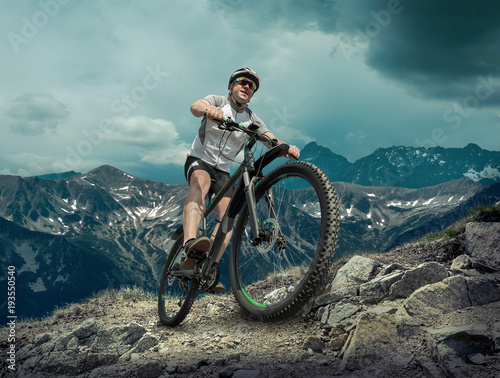 Man in helmet and glasses stay on the bicycle under sky with clo #193550540