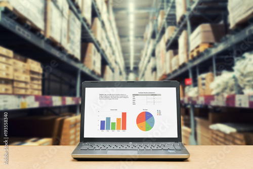 Fotografía  Laptop with analysis sale screen on table with blur warehouse cargo in factory