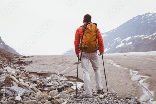Male hiker standing with backpack on a sunny day