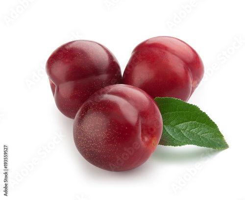 Three red plums with a leaf
