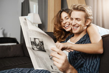 Happy And Attractive Couple In Love Reading Newspaper At Home And Laughing Sincerely While Girlfriend Hugging Boyfriend In Living Room. Partners Looking At Funny Caricature