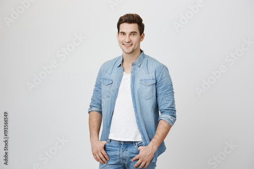 Fotografía  Handsome unshaven adult with happy and self-assured expression, looking at camera while holding hands in pockets, isolated over white background