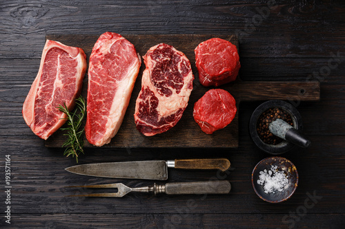 Photo Stands Meat Variety of Raw Black Angus Prime meat steaks Blade on bone, Striploin, Rib eye, Tenderloin fillet mignon on wooden board