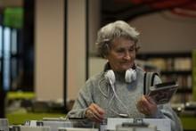 Senior Woman Choosing A Dvd Cassette