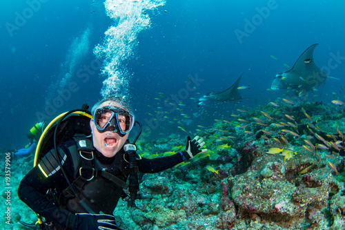 scuba diver yelling oh my god at Manta in the blue ocean background portrait