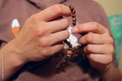 Female hands holding wooden rosary. Close up