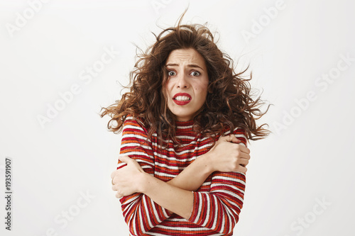 It is freezing cold outside. Indoor shot of poor attractive girl with curly hair that flows on wind, hugging herself and trembling, standing without coat on windy weather over gray background