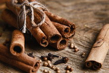 Cinnamon Sticks On Wood Table With Bundles Of Cinnamon, Coriander, Cloves, In Soft Focus In Wooden Background, Macro Vintage