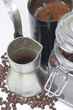 Cezve stand on a white surface. Next to a glass jar with coffee beans and a coffee grinder with ground coffee.