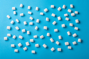 Sweet Marshmallows on blue background with a shadow. Flat lay top view
