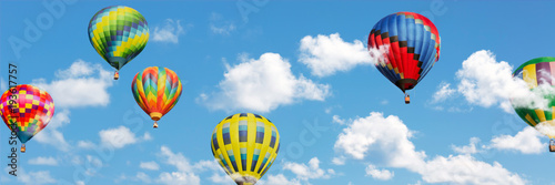 Multi colored hot air balloons in white clouds over blue sky
