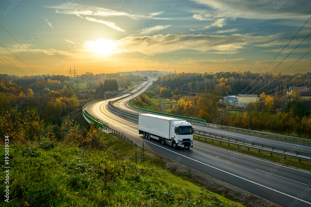 Fototapeta White truck driving on the highway winding through forested landscape in autumn colors at sunset