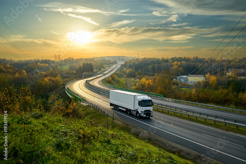 Fotografía  White truck driving on the highway winding through forested landscape in autumn