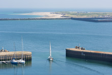 Sailing Ship Leaving Harbor Of Helgoland, German Island In The Northsea. At The Horizon The Smaller Island Dune.