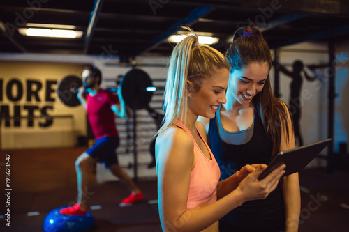 Attractive girl using tablet computer in the gym.