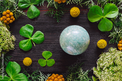 Obraz na plátne  Green Aventurine Sphere with Shamrocks and Mixed Foliage