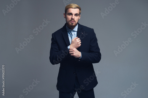 Foto op Plexiglas Artist KB Fashionable and brutal. Handsome business man adjusting the cuffs in front of the grey background.