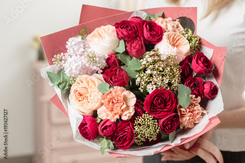 bouquet of highly red coloured . beautiful luxury bunch of mixed flowers in womans hand. the work of the florist at a flower shop. © malkovkosta