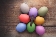 Wooden Cross Above The Colored Easter Eggs On Wooden Background