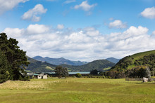 Farm House And Paddock In Rural Otago Peninsula, New Zealand, With Coastline And Mountains In Distance