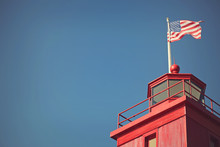 US Flag On Top Of A Red Lighthouse