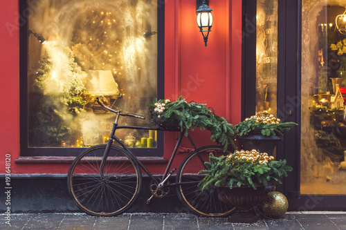 Papiers peints Velo Christmas decorated showcase with old bicycle, fir branches, glass shiny toys and vintage lantern. Red building facade