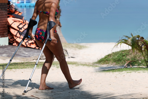 Injured tourist with crutch to supporting themself relax on the beach summer Fototapete