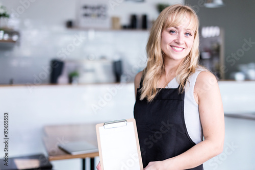 Fotografía  business owner caucasian woman is holding menu wear apron with coffee shop backg