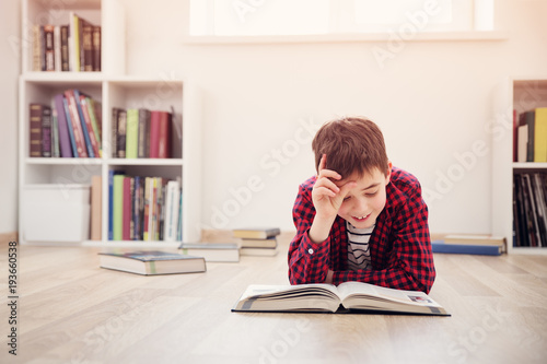 Fotografie, Obraz  Eight years old child lying on the floor among books at home