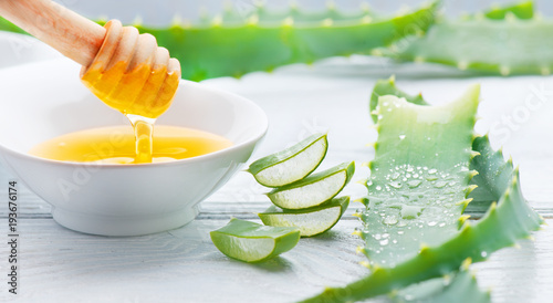 Aloe Vera with honey closeup on white wooden background. Sliced Aloevera natural organic renewal cosmetics, alternative medicine. Aloe vera gel, organic skincare concept