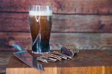 Portion Of Beef Jerky Cutting Into Slice On A Cutting Table With Dark Beer Glass And A Kitchen Knife On Vintage Wooden Background, Man Standing Behind
