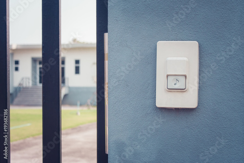 Fotografie, Obraz  Close up white doorbell or buzzer button on concrete wall beside doorway with house in the background