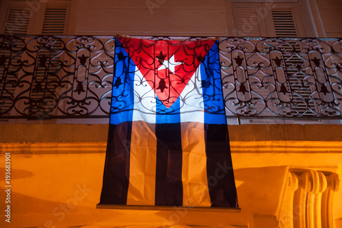 Cuban flag hanging over a balcony in Havana at night Canvas Print
