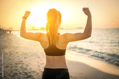 Fotografie, Tablou  Back view of strong sporty girl showing muscles at the beach during sunset