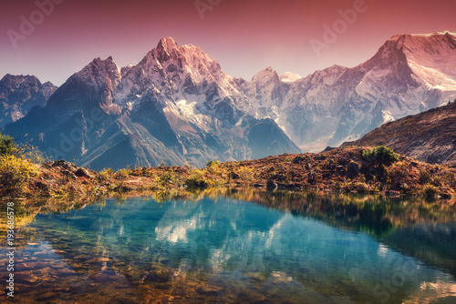 Tuinposter Reflectie Beautiful landscape with high mountains with snow covered peaks, red sky reflected in lake. Mountain valley with reflection in water in sunset. Nepal. Amazing scene with Himalayan mountains. Nature