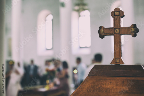 Obraz Wedding event in a church the old wooden cross is in a first view and the people are blurred in the background - fototapety do salonu