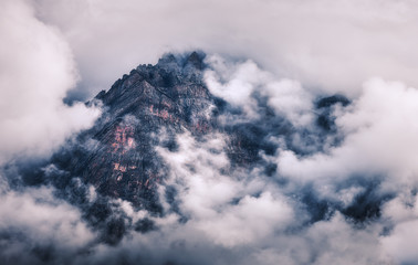 Panel Szklany Góry Mountains in clouds in overcast evening in Nepal. Landscape with beautiful high rocks and dramatic cloudy sky at sunset. Nature background. Fairy scene. Amazing mountains at dusk. Vintage style