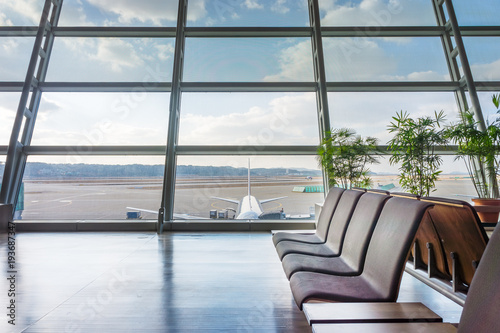 Foto op Aluminium Luchthaven Seats in concourse area in airport. Near parking position of an airplane.