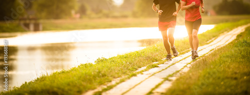 Leinwand Poster Couple running outdoors, at sunset, by a river, staying active and fit