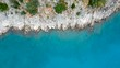 Aerial view looking straight down onto rocky cliffs on a clear turquoise coastline panning to the right
