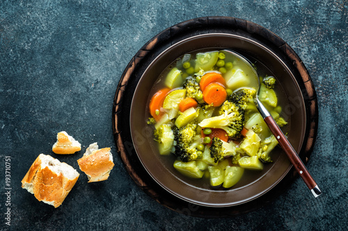 plate of fresh hot vegetable soup with broccoli, potato, green peas, onion and carrot. healthy vegan diet food, top view