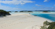 A tropical island with two dinghies and fresh footprints making for a private beach walk. Located near the sailboat anchorage of Norman's Cay in the Bahamas.