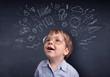 Little boy in front of a drawn up blackboard