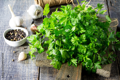 Sprigs of fresh parsley, garlic and various spices on the rustic kitchen table.