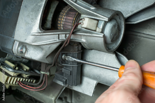 hand of a repairman with a screwdriver repair of the electric motor of the washing machine, replacement of brushes, home appliances repair & services concept