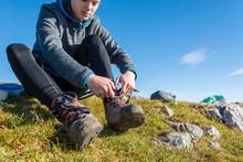 Female Hiker Tying Boots.
